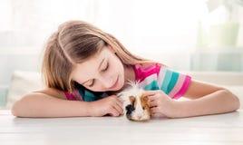 Девушка штрихуя пушистую морскую свинку Стоковая Фотография RF