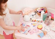 Девушка шьет куклы платья от частей ткани Стоковая Фотография RF