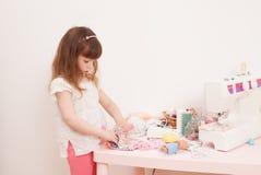 Девушка шьет куклы платья от частей ткани Стоковые Фотографии RF