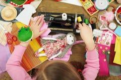Девушка шьет одежды куклы, взгляд сверху, шить аксессуары взгляд сверху, рабочее место белошвейки, много возражает для needlework Стоковые Изображения