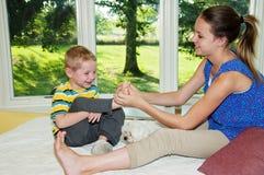Девушка щекоча ногу childs стоковые фото