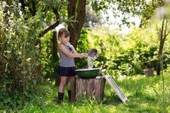 Девушка льет воду в таз от ветроуловителя Стоковое Фото