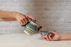 Девушка льет чай для человека в азиатском кафе в чайнике стоковое фото rf