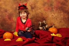 Девушка дьявола имеет потеху на хеллоуин с тыквами и шляпой Стоковое Изображение RF