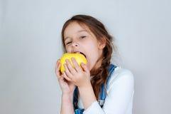 Девушка эмоционального портрета маленькая красивая с отрезками провода в прозодеждах джинсов есть укусы держа яблоко 6-7 лет студ стоковое изображение