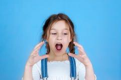 Девушка эмоционального портрета маленькая красивая с отрезками провода в прозодеждах джинсов есть укусы держа яблоко 6-7 лет студ стоковые фото