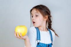 Девушка эмоционального портрета маленькая красивая с отрезками провода в прозодеждах джинсов есть укусы держа яблоко 6-7 лет студ стоковые фотографии rf