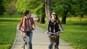Девушка Active 2 едет совместно в парке города Усмехаясь молодые женщины с велосипедами Outdoors акции видеоматериалы