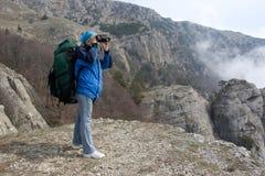 девушка backpack бинокулярная она используя Стоковые Фото