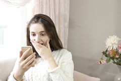 Девушка Confuset читая сообщение в умном телефоне сидя на кресле дома стоковые фото