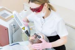 Девушка cosmetician в изумлённых взглядах делает процедуру шелушения углерода с помощью лазеру косметологии Сторона углерода стоковые изображения
