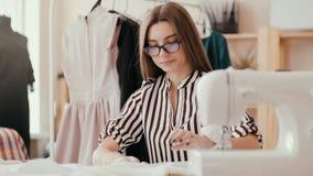 Девушка dressmaker приглаживает ткань на таблице с ее руками и делает метку с карандашем На переднем плане a акции видеоматериалы