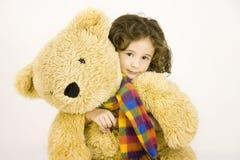 девушка embraces медведя большая меньший игрушечный стоковое изображение rf