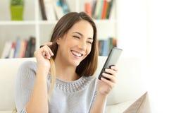 Девушка flirting на линии с умным телефоном стоковая фотография