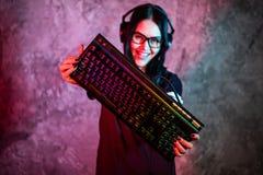 Девушка Gamer играя с компьютером дома Молодой женский представлять с клавиатурой компьютера стоковое фото