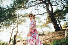 Девушка hippie в красивом платье летания, шляпе и круглых стеклах в сосновом лесе среди гор стоковая фотография