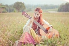Девушка Hippie играя гитару на траве Стоковое Фото
