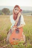 Девушка Hippie играя гитару на траве Стоковые Изображения RF