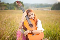 Девушка Hippie играя гитару на траве Стоковые Фото