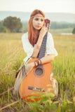 Девушка Hippie играя гитару на траве Стоковое Изображение