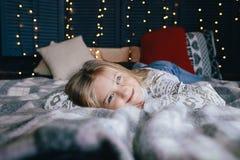 Девушка Ittle в свитере на кровати на зимний день Стоковые Фотографии RF