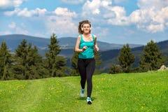 Девушка jogging на следе в горах на поле с травой в дне лета солнечном стоковые фото