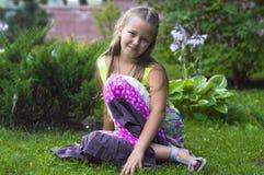 Девушка Liitle сидя на траве Стоковые Фотографии RF