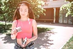 Девушка Melomaniac держит cassete и смотрит ее Она раскрывала игрока в ее руках Девушка решила положить cassete Стоковые Фотографии RF
