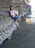 Девушка Millenial азиатская представляя вдоль берега и против стены с шариком, камерой, и крышкой лета Стоковое Изображение RF