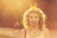 Девушка pin-вверх держа леденец на палочке на заходе солнца Стоковое Изображение RF