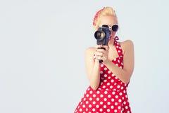Девушка pin-вверх при красное винтажное платье держа год сбора винограда камера 8 mm стоковые изображения