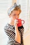 Девушка Pinup с красными губами пригвождает выпивая кофе или чай держа красную чашку & смотря камеру над белыми шторками солнца Стоковая Фотография