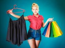 Девушка Pinup с хозяйственными сумками покупая юбку сбывание Стоковые Изображения RF