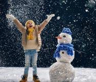 Девушка plaing с снеговиком Стоковое фото RF