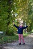 Девушка Preschooler в парке осени с кленовыми листами Стоковая Фотография RF