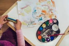 Девушка, preschooler, крася с цветом воды стоковое изображение
