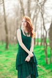 Девушка Redhead в зеленом платье в парке стоковая фотография rf