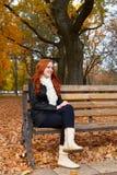 Девушка Redhead в парке города осени, сидит на деревянном стенде, одном люд Стоковая Фотография RF