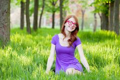 Девушка Redhead в eyeglasses сидя на зеленой траве Стоковая Фотография