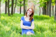 Девушка Redhead в eyeglasses сидя на зеленой траве Стоковые Фото