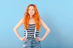 Девушка Redhead жмурится и хмуриться Сомнение, выбор и подозрение стоковое фото