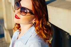 Девушка Redhead идя в город Она усмехающся и беспечальна вскользь тип Стоковое Изображение