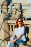 Девушка Redhead идя в город Она усмехающся и беспечальна вскользь тип Стоковые Изображения