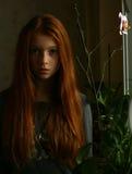 Девушка Redhead мечтая на окне Стоковые Фото