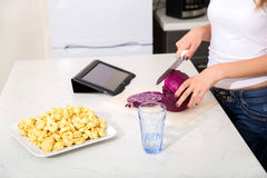 Девушка Redhead отрезая в ПК таблетки кухни наблюдая Стоковое Изображение RF