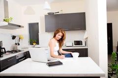 Девушка Redhead работая в кухне Стоковые Изображения