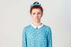 Девушка Redhead смотря прочь, имеющ сомнительное и нерешительное выражение стороны, следуя ее губы если запрещенный сказать что-н Стоковое фото RF