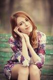 Девушка redhead стиля сидя на стенде стоковые изображения
