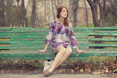 Девушка redhead стиля сидя на стенде стоковое фото rf