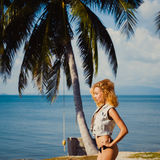 Девушка redhead tan Oung тонкая сексуальная на предпосылке голубого неба в ладони моря лета Стоковое Изображение